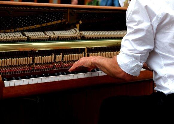 Pianist speelt op open piano